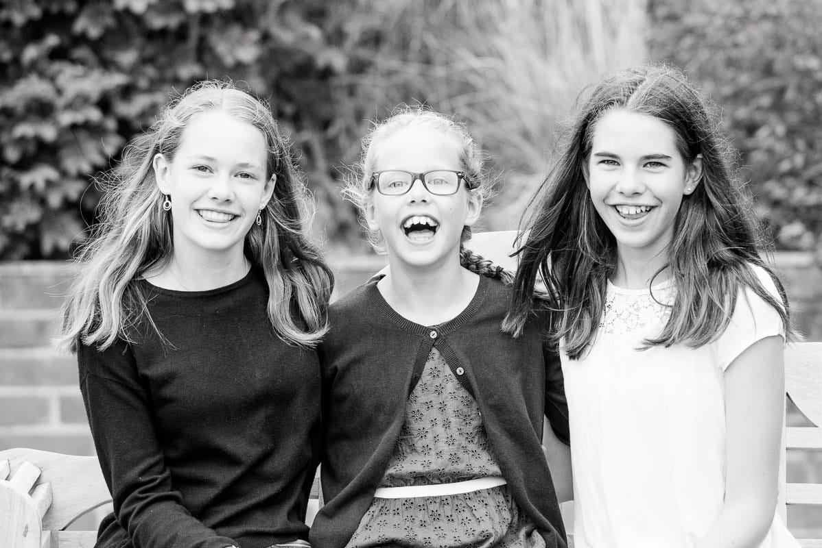 black and white photo of three sisters laughing