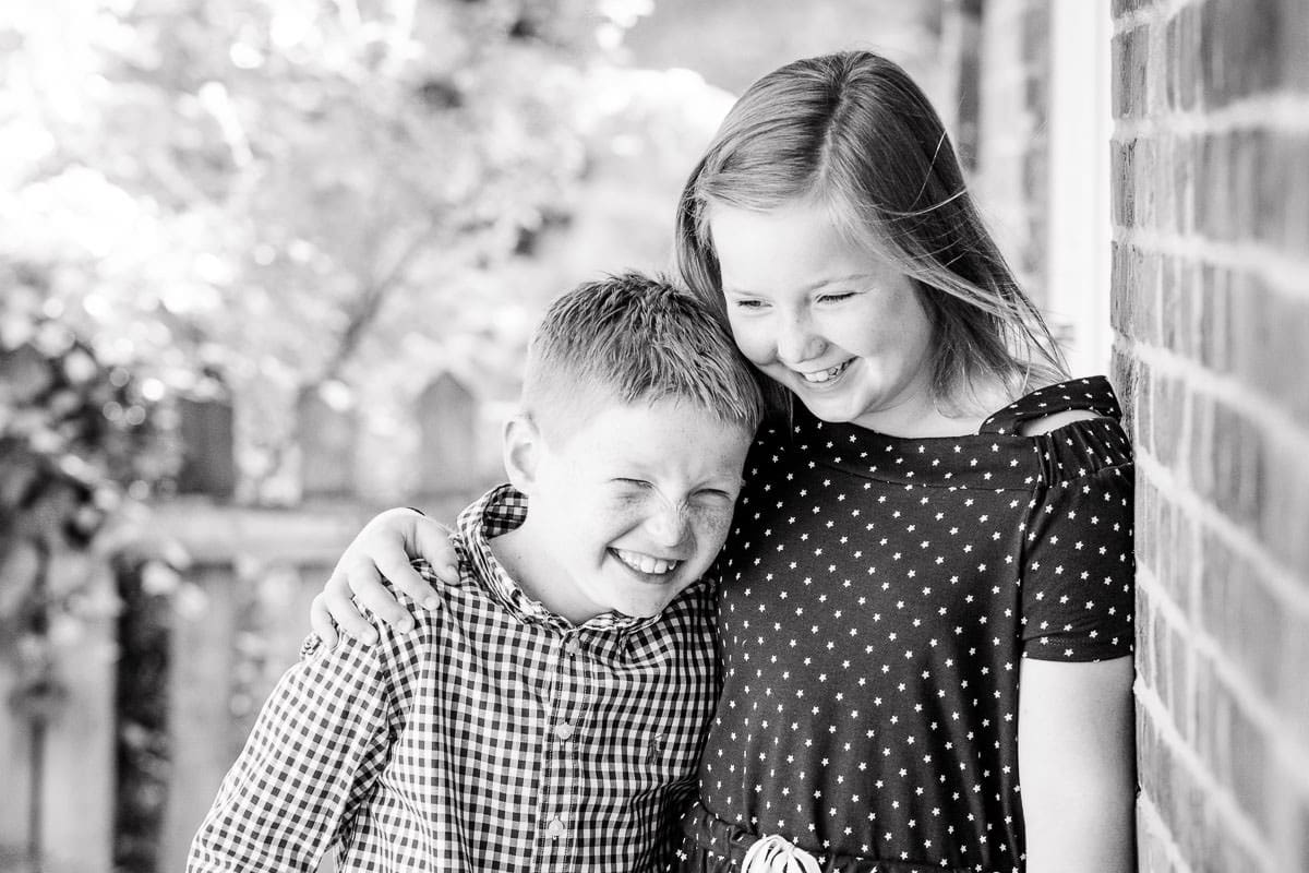black and white photo of a brother and sister cuddling and laughing