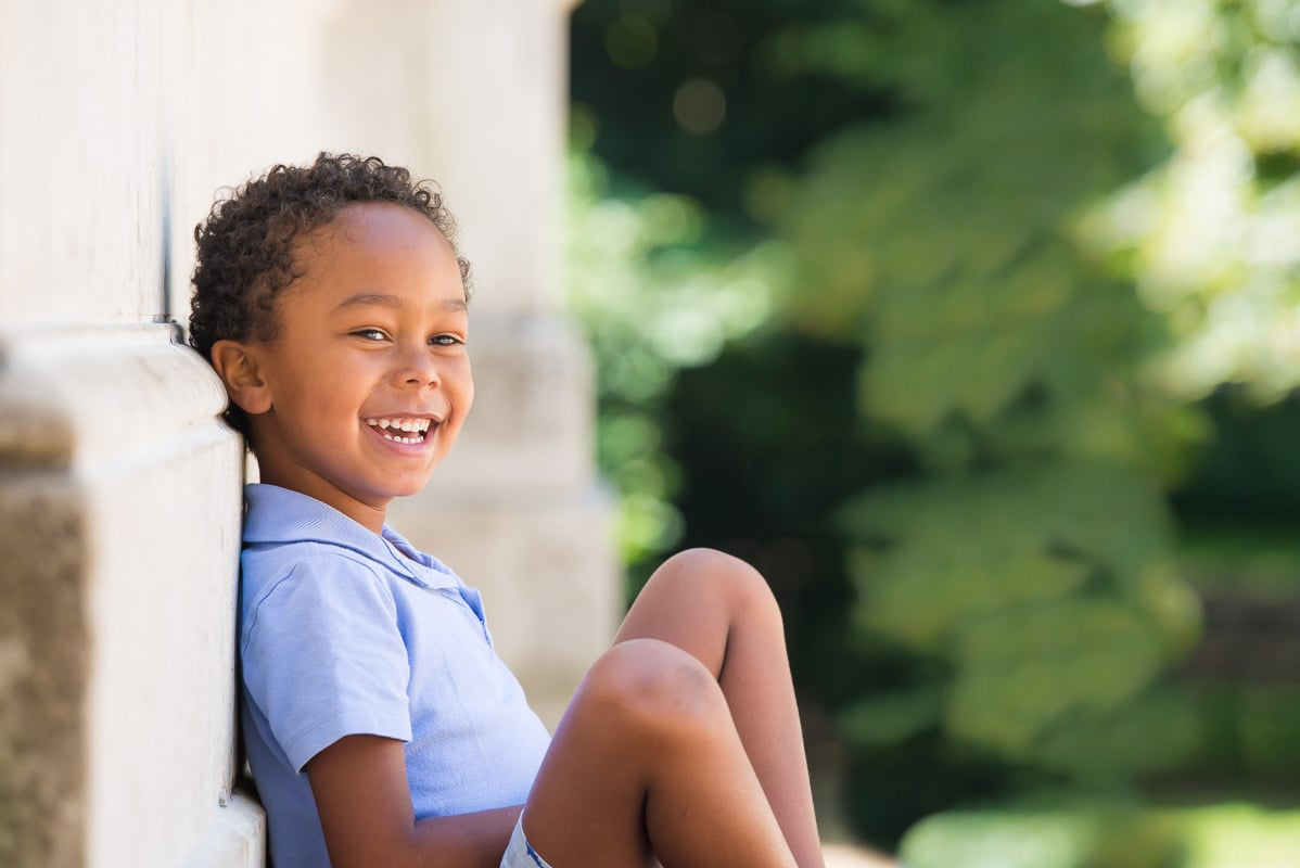 Young boy wearing a blue t-shirt sitting against a stone wall and smiling at the camera
