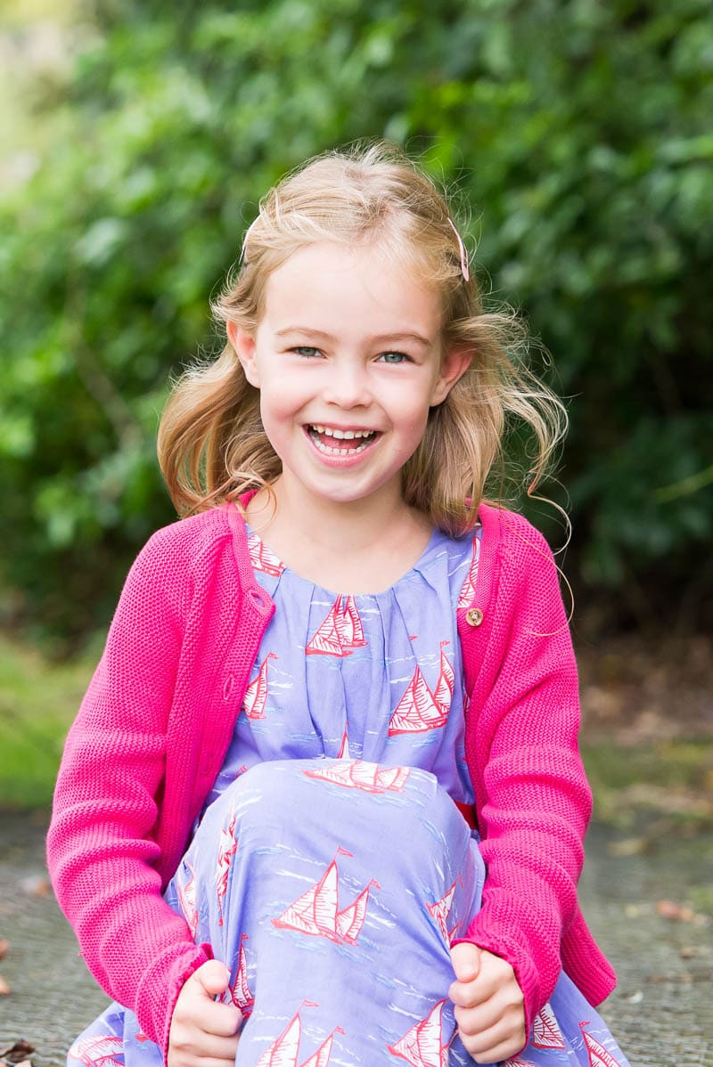 Young girl wearing pink cardigan laughing
