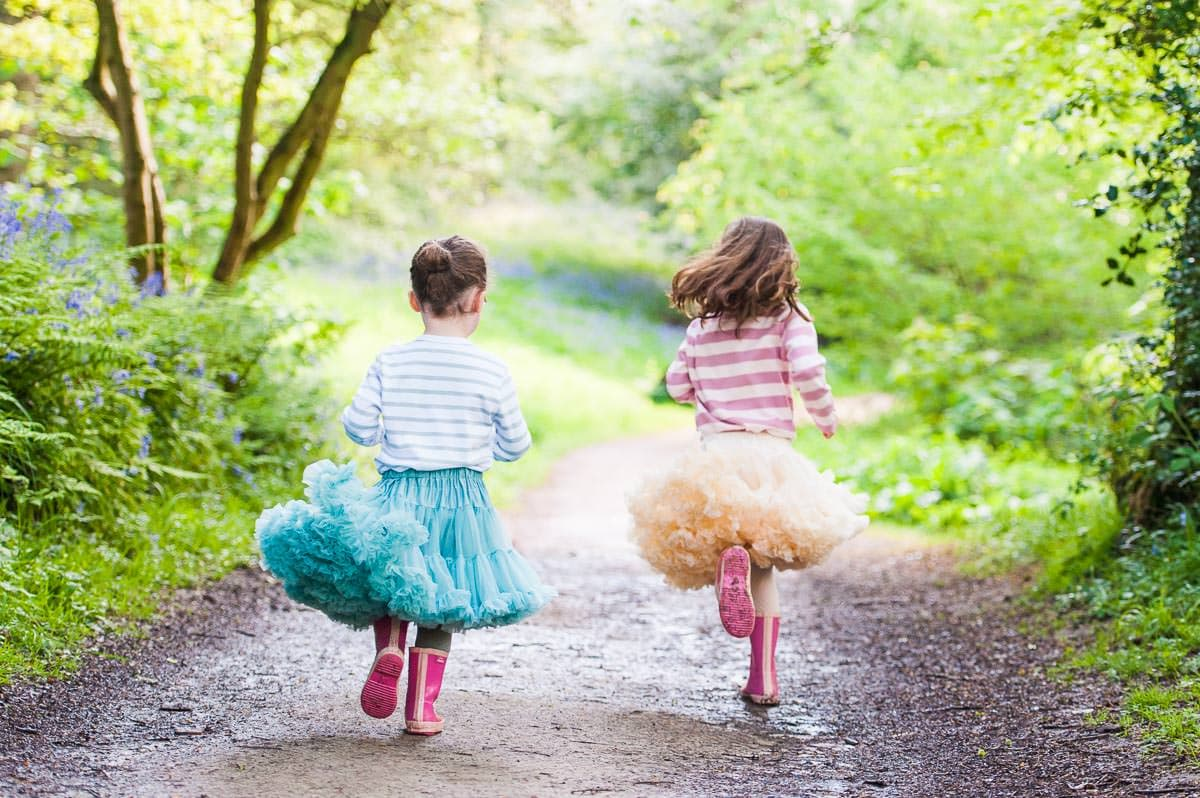 Two young girls running through the woods wearing tutus