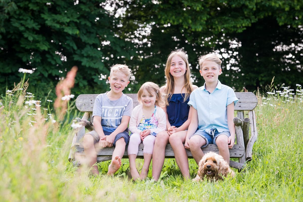 Four siblings sitting on a bench laughing