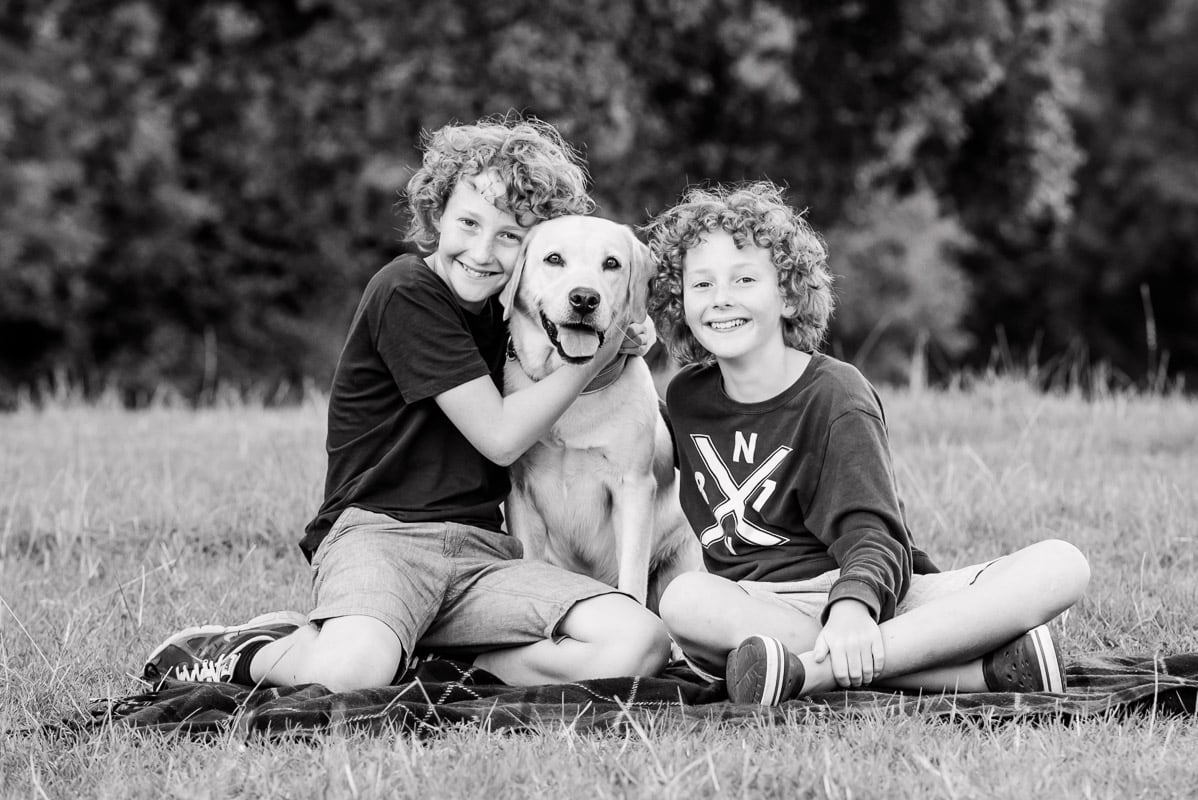 b/w picture of twin boys hugging their dog