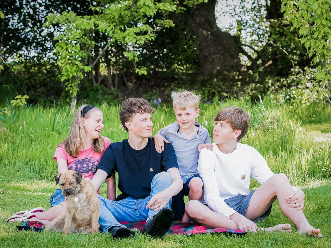 Four siblings sitting on the grass laughing