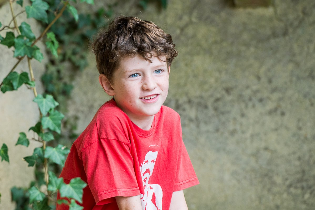 boy wearing red t-shirt sitting in vine