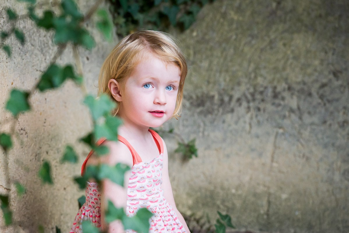 Young girl with amazing blue eyes sitting behind a vine