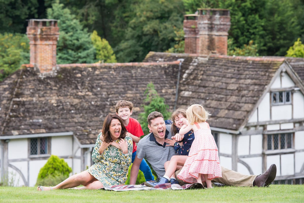 Family sitting on lawn laughing with children