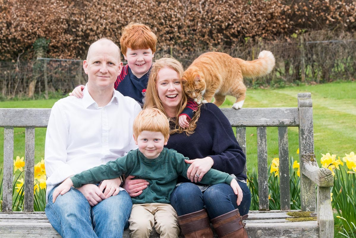 Family with ginger hair sitting on a bench with ginger cat