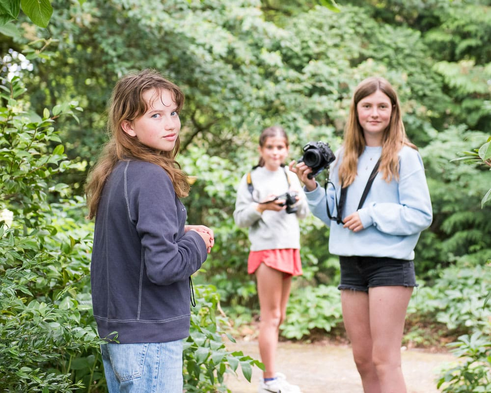 Teenagers holding cameras on a photography course at Borde Hill Gardens