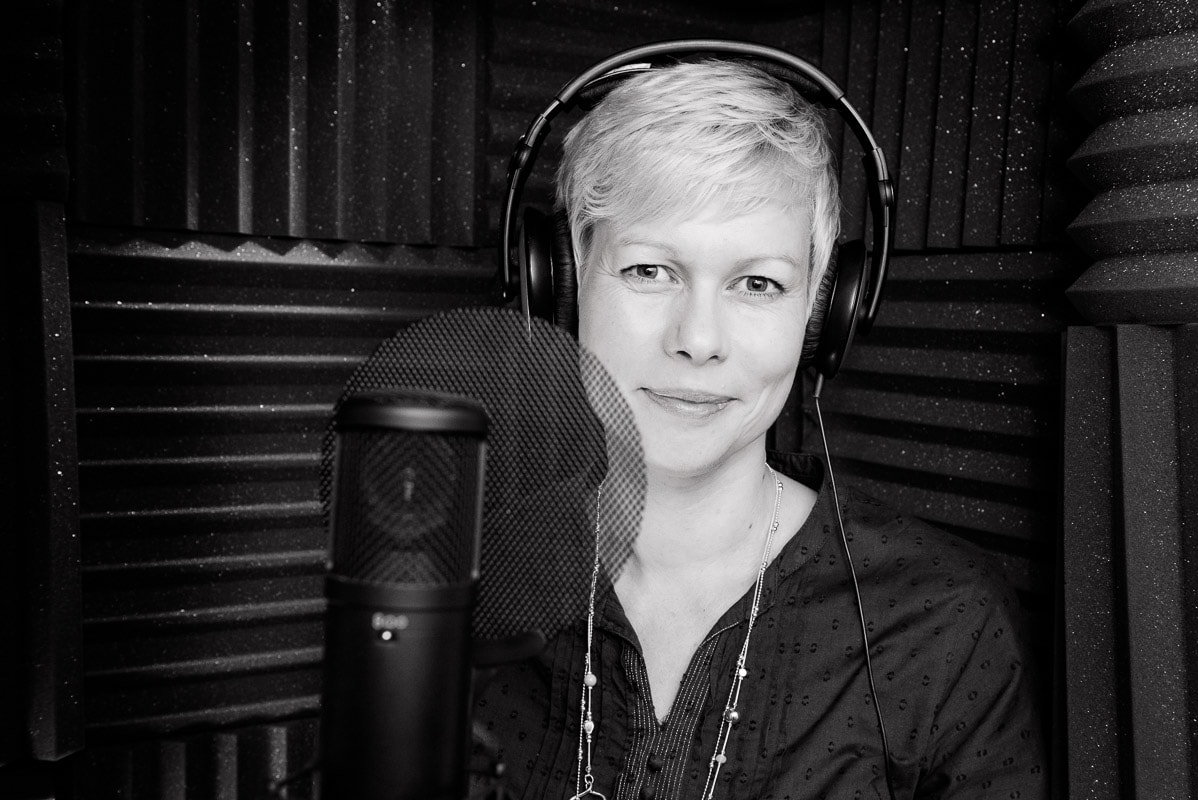 Woman wearing headphones in a recording booth