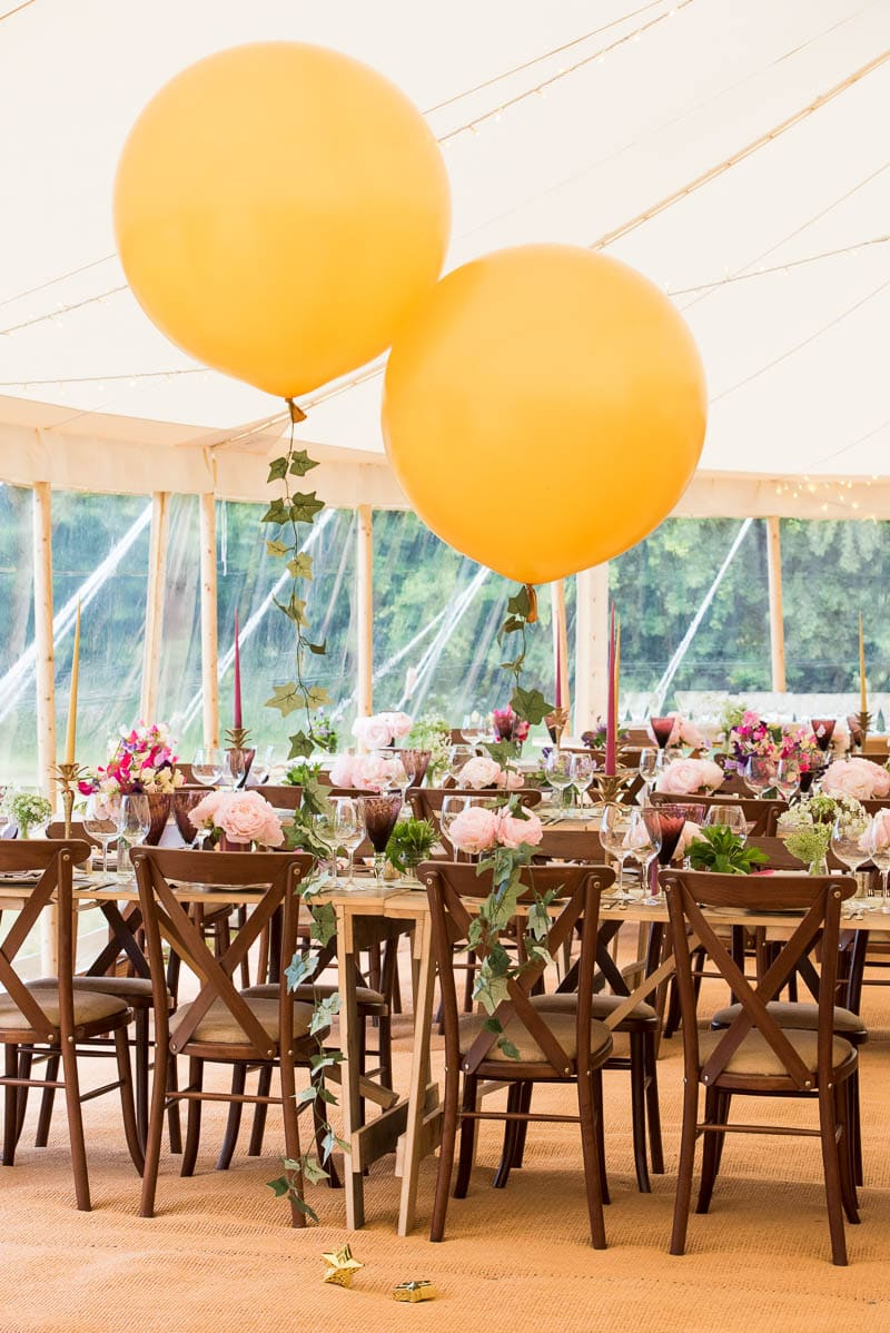 Balloons and decorated tables inside a marquee