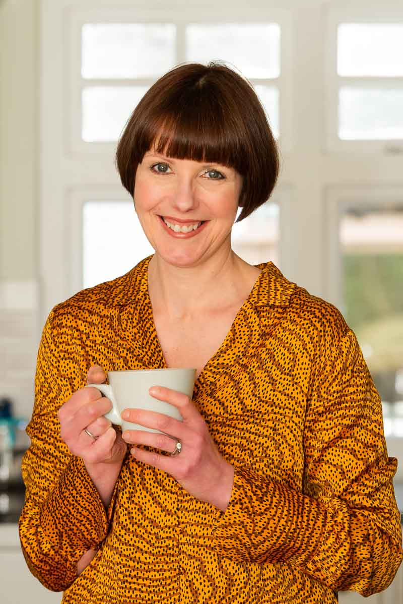 woman wearing yellow holding cup of tea