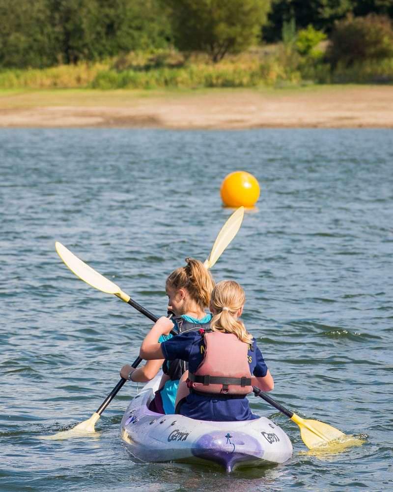 Girls kayaking on reservoir