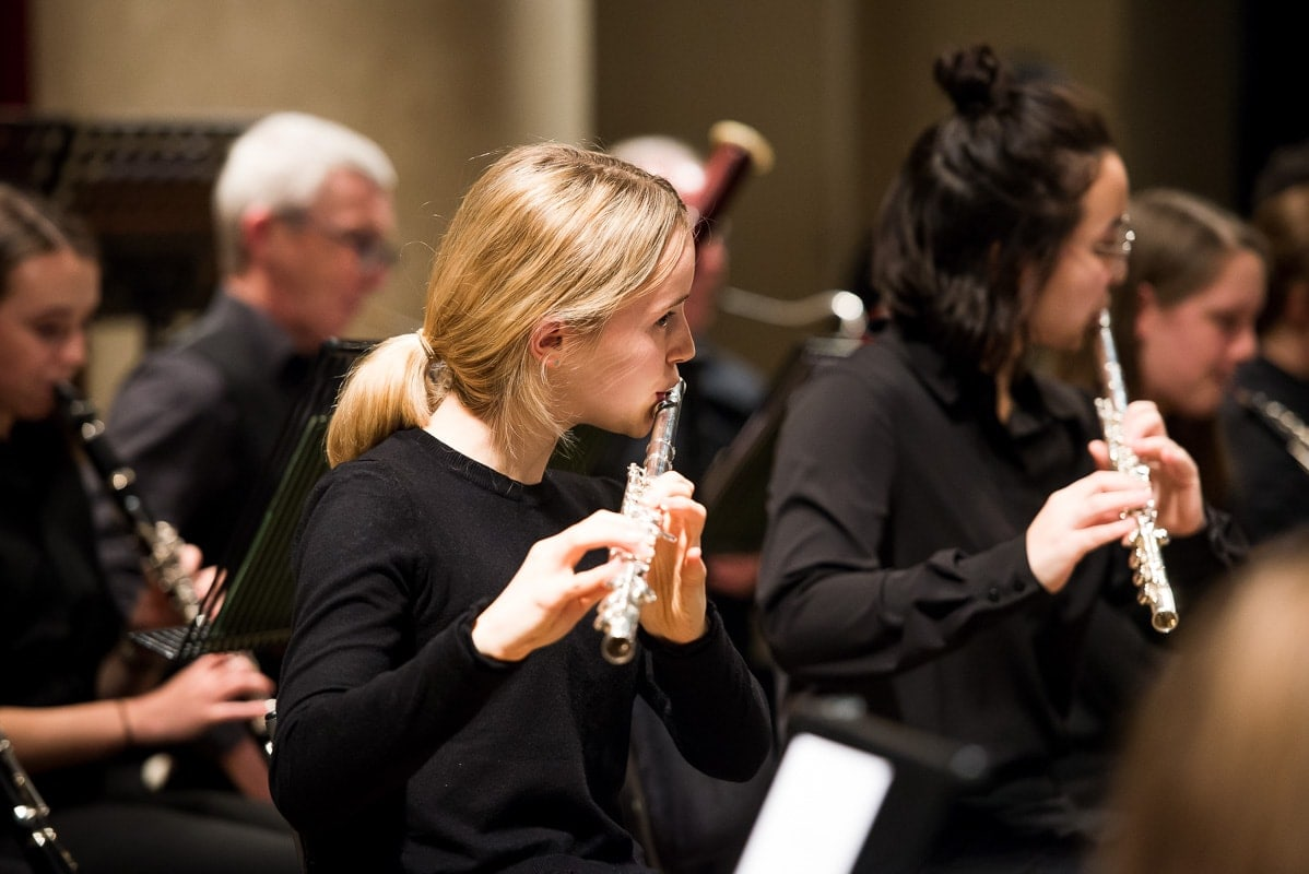 Teenage girl playing flute in orchestra