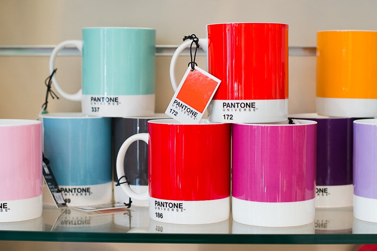 Brightly coloured mugs sitting on a shop shelf