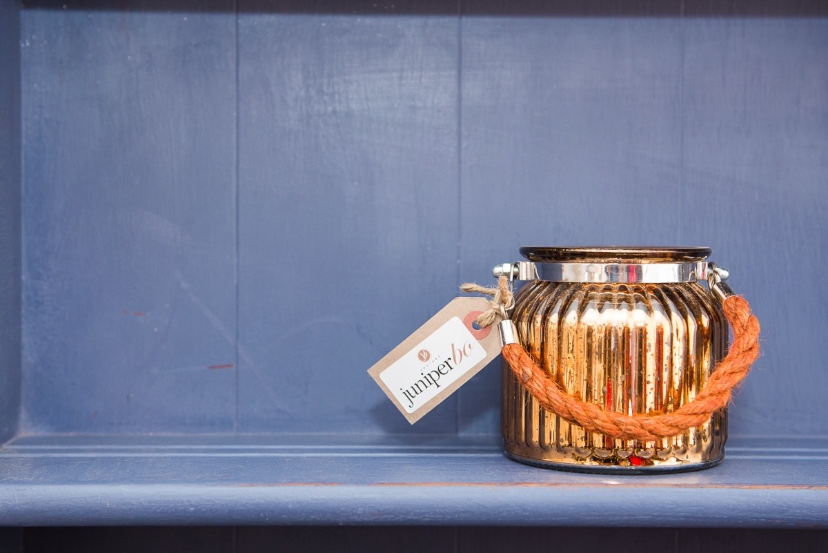A shiny gold vase sitting on a blue shelf