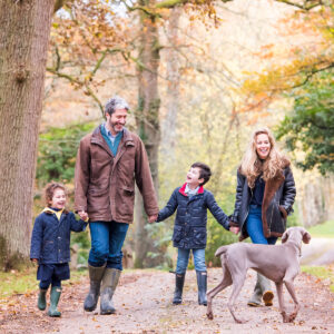 family of four walking with dog in Autumn