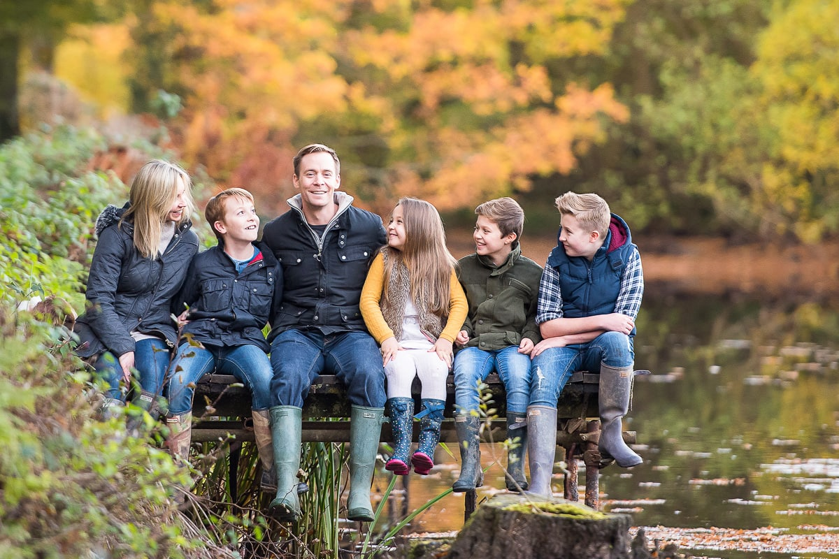 Family sitting on a jetty during autumn