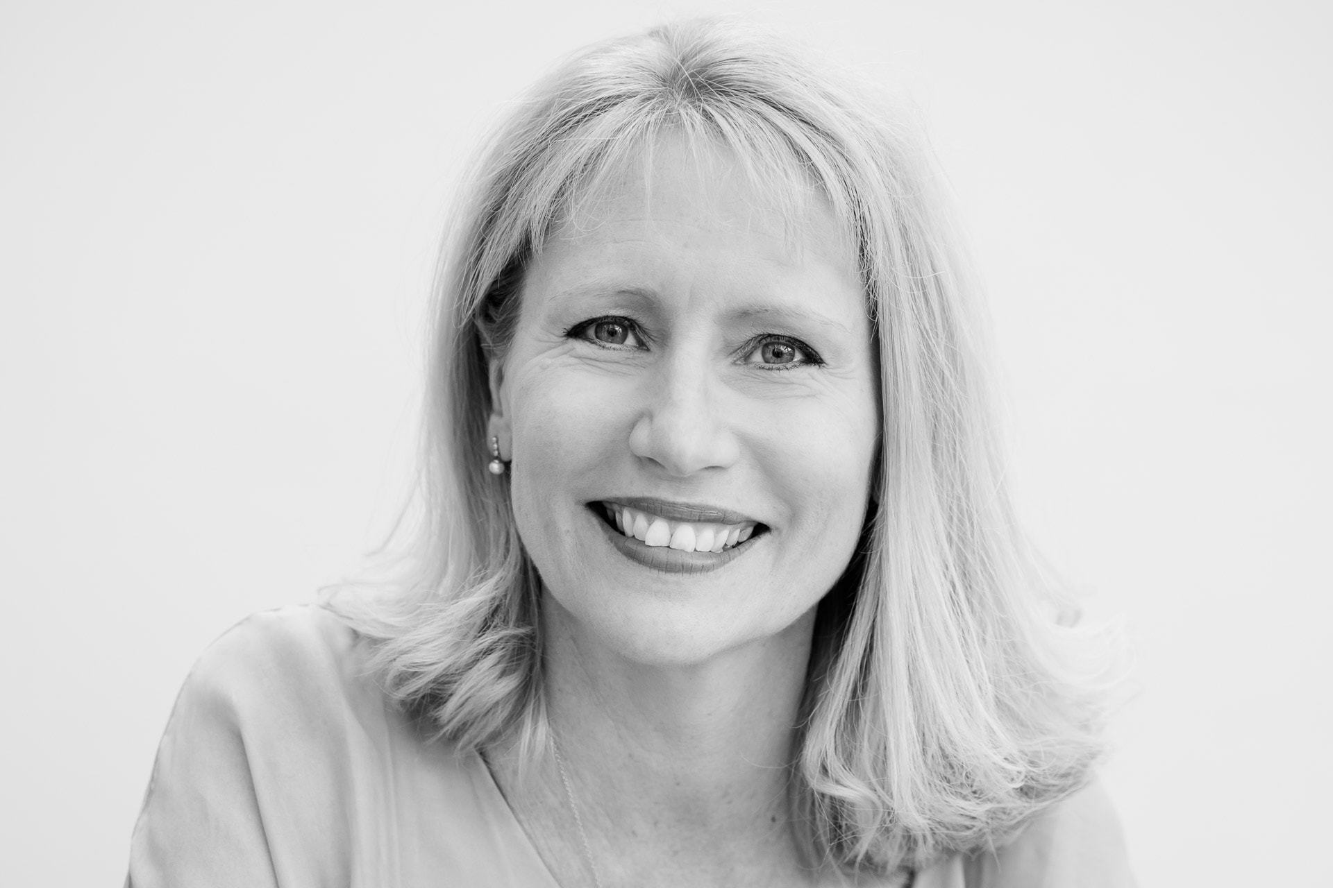 relaxed and natural, black and white business headshot of a woman smiling at the camera