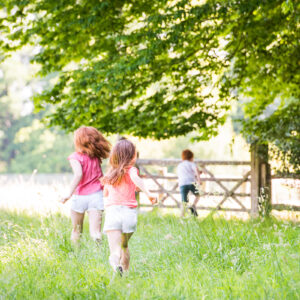 relaxed picture of 3 children running through summer meadow in West Sussex
