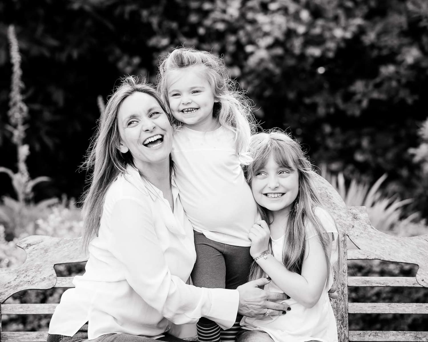 Black and white picture of two girls sitting on a bench and laughing with their mother