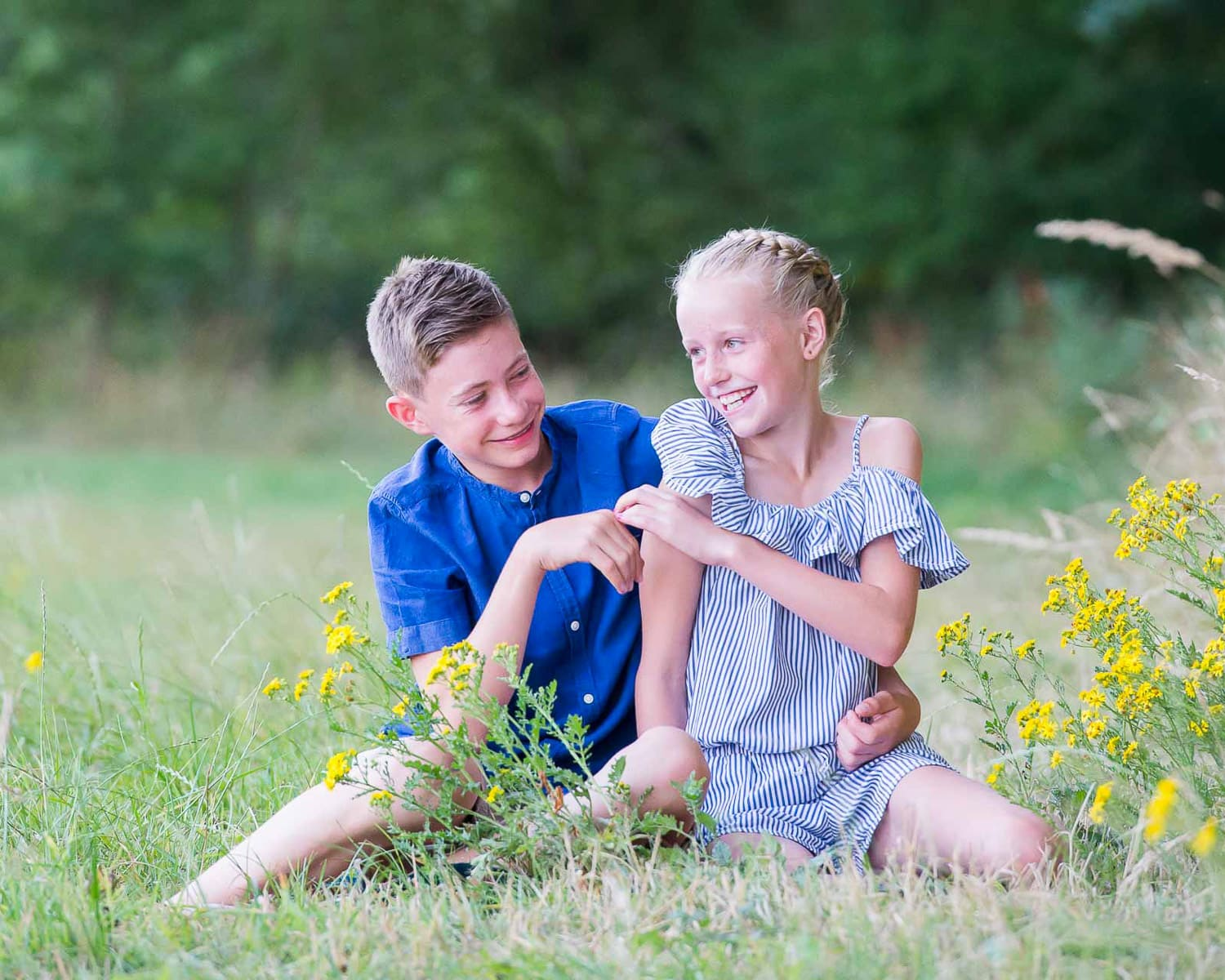 two teenage children sitting next to each other and laughing in a Sussex meadow