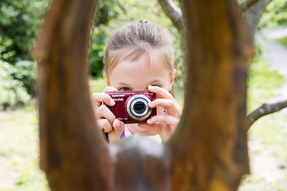 Young girl taking a picture using a red camera through a gap in a tree at a garden in Sussex