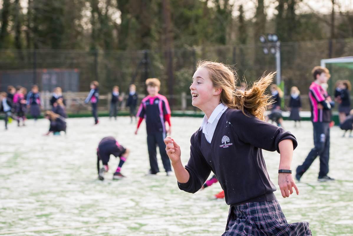 school girl running across playground
