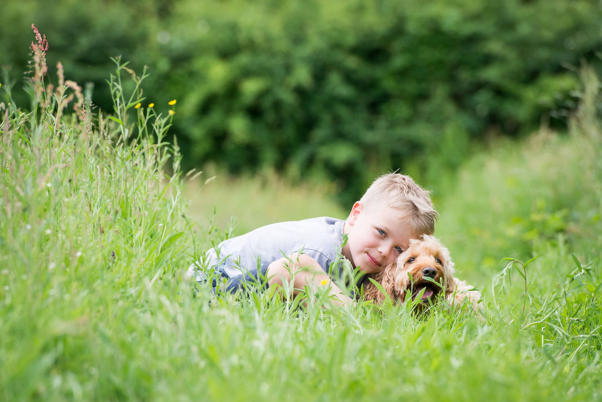Young boy laying on the grass during his family photoshoot with his dog