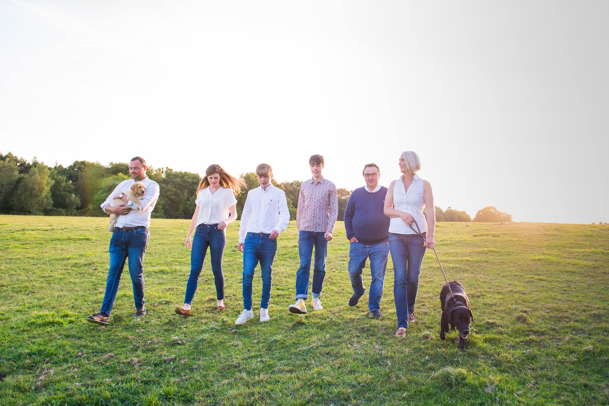 Family waking in the sunshine with their dog on a family photoshoot