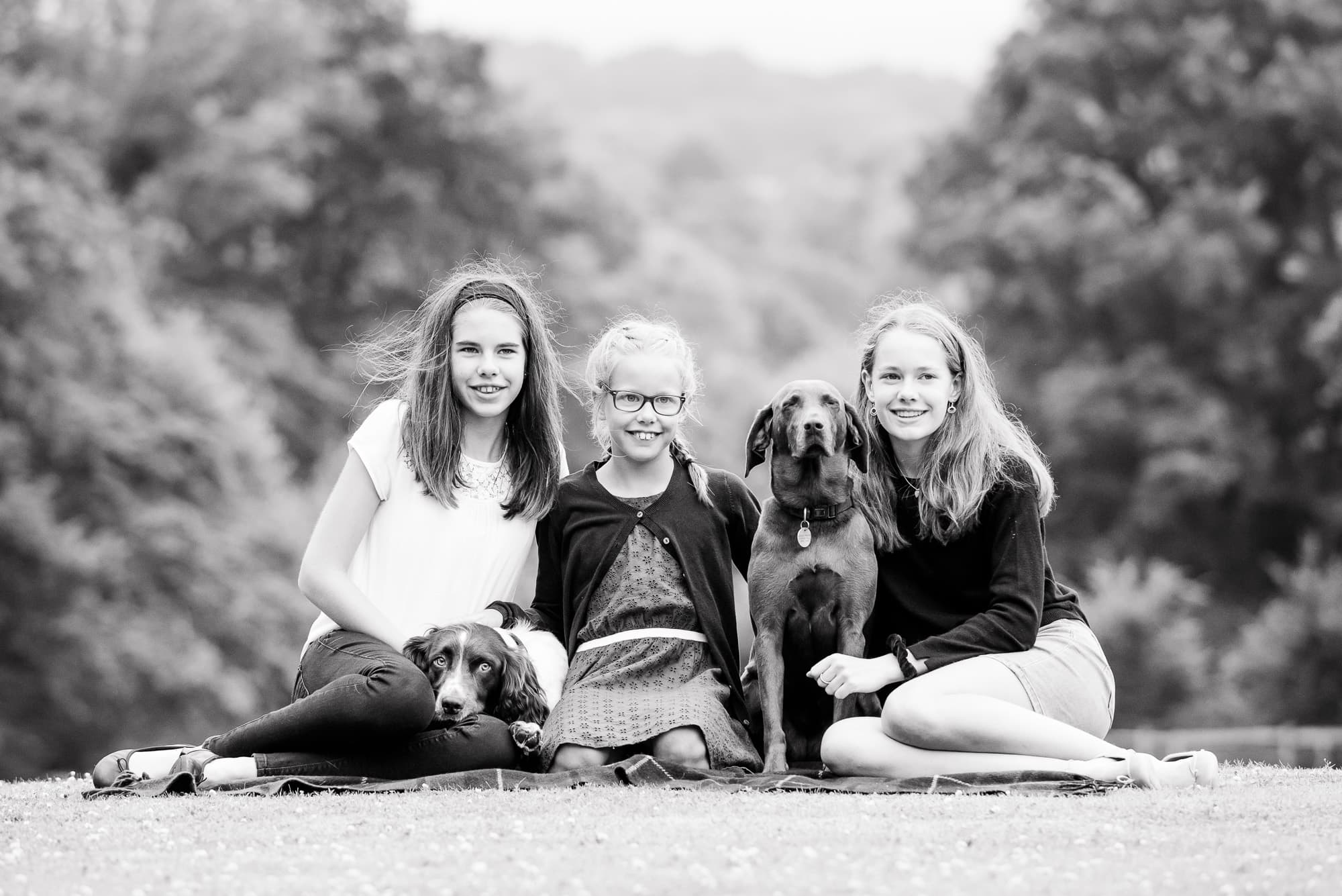 Black and white photograph of three teenager sisters sitting on a lawn with their two dogs