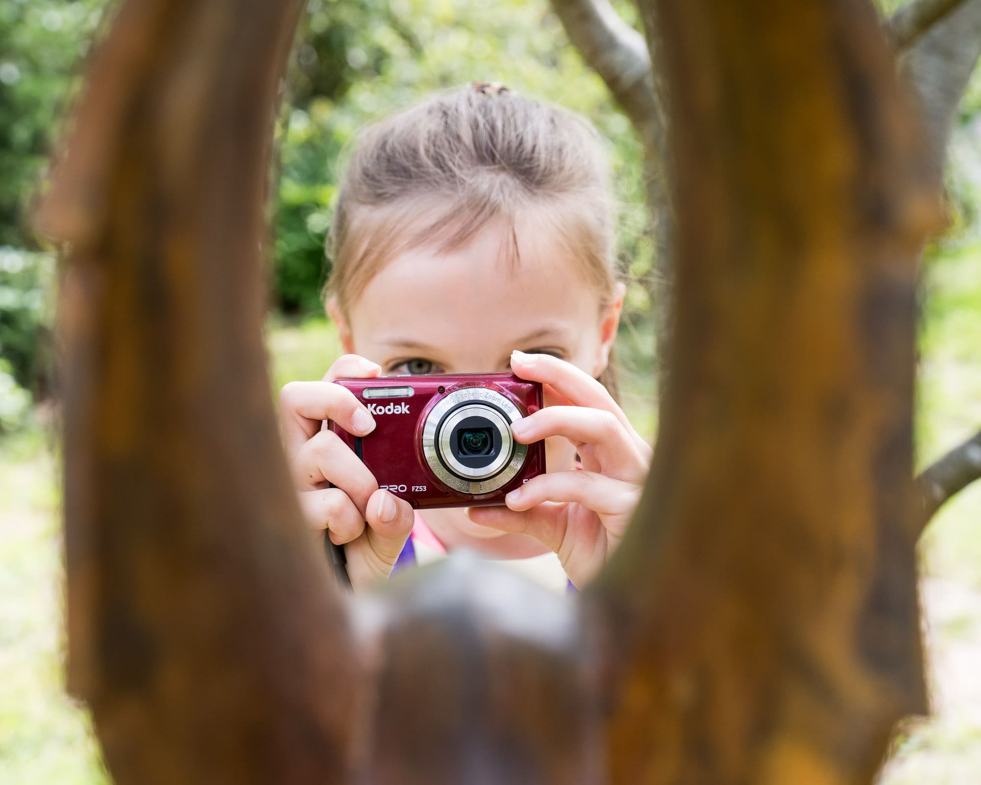 Young girl holding a red camera peeking through a gap in a tree trunk
