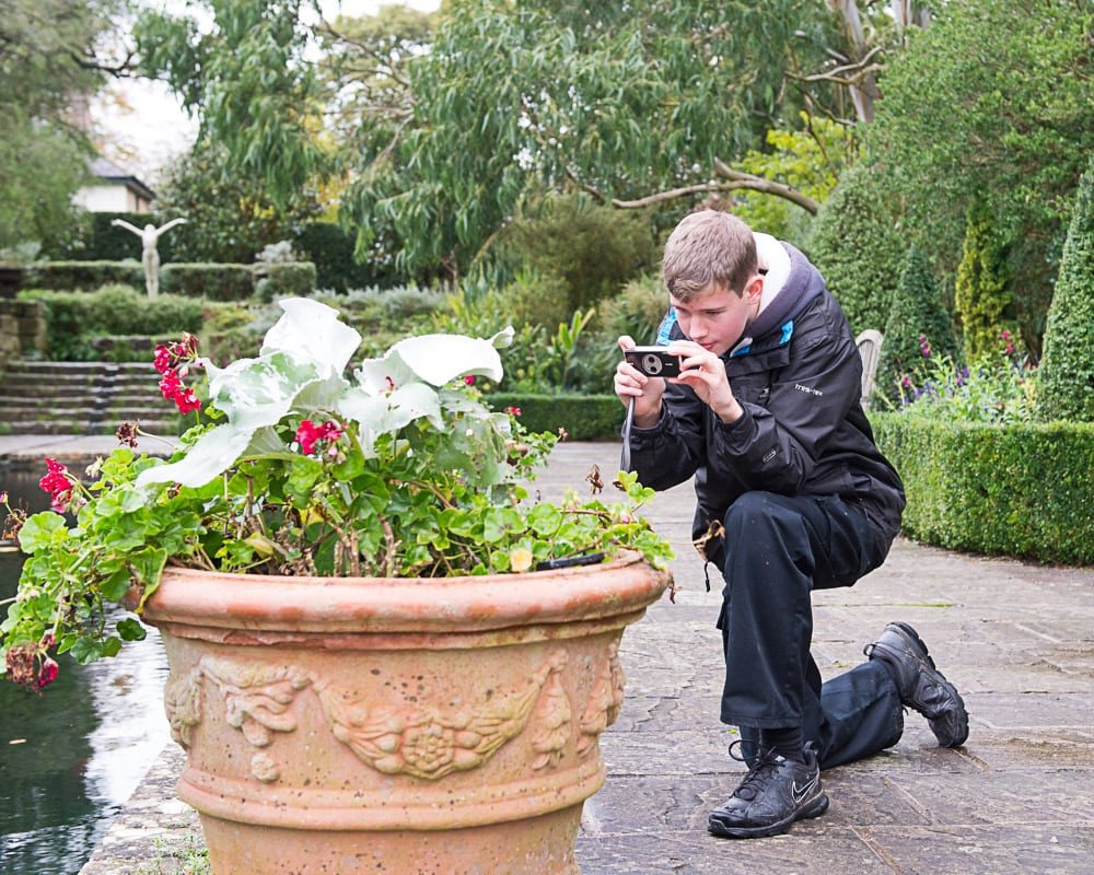 teenage boy photographing flowers at Borde Hill Garden, Sussex
