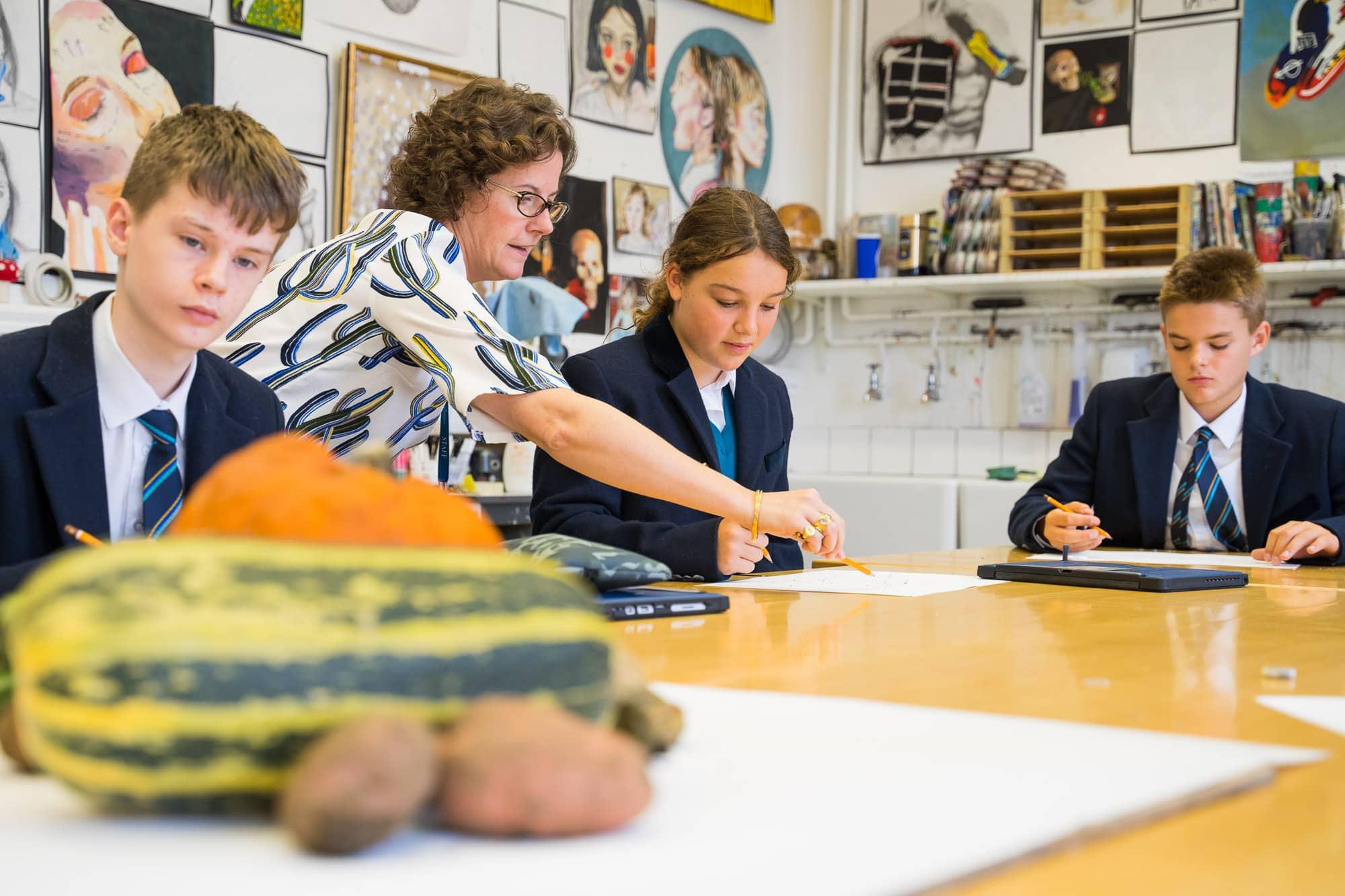 art teacher teaching students how to paint vegetables
