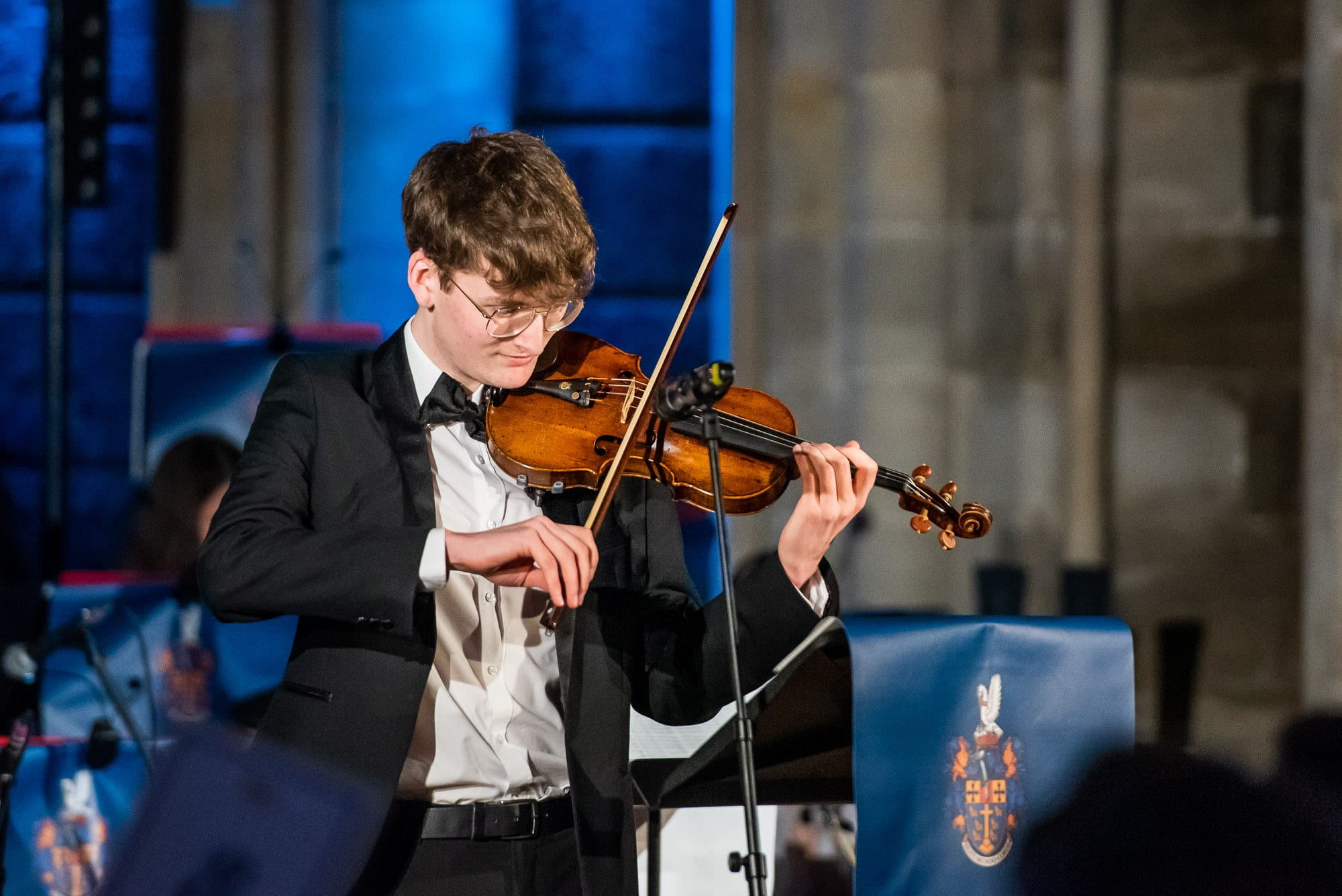 teenage student playing the violin in school concert