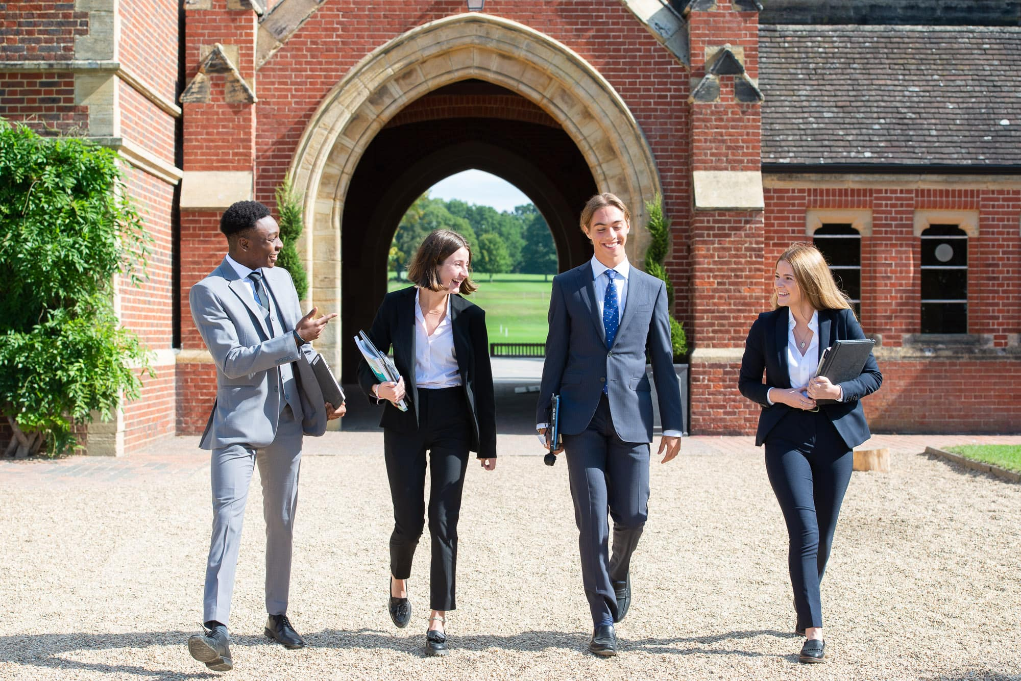 Group of teenage students walking through the arch of Ardingly College
