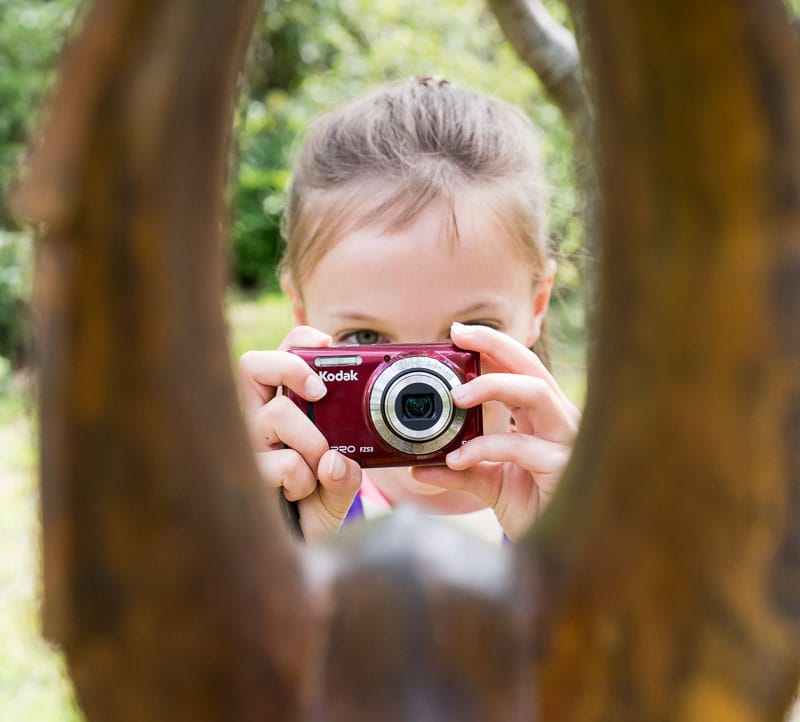 Young girl using a camera on a photography course