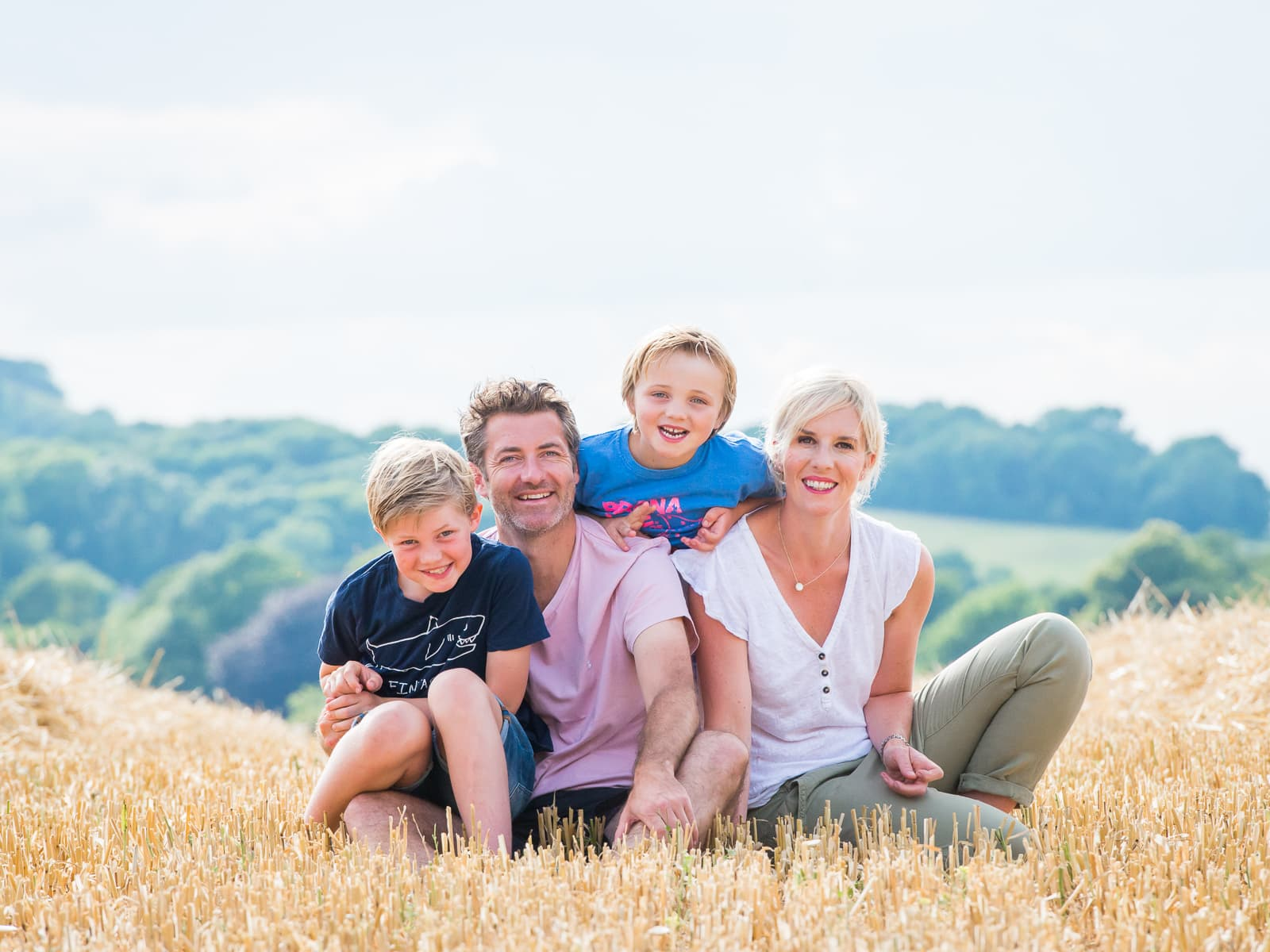 A family sitting in a field of corn during a family photoshoot in Ditchling, Sussex
