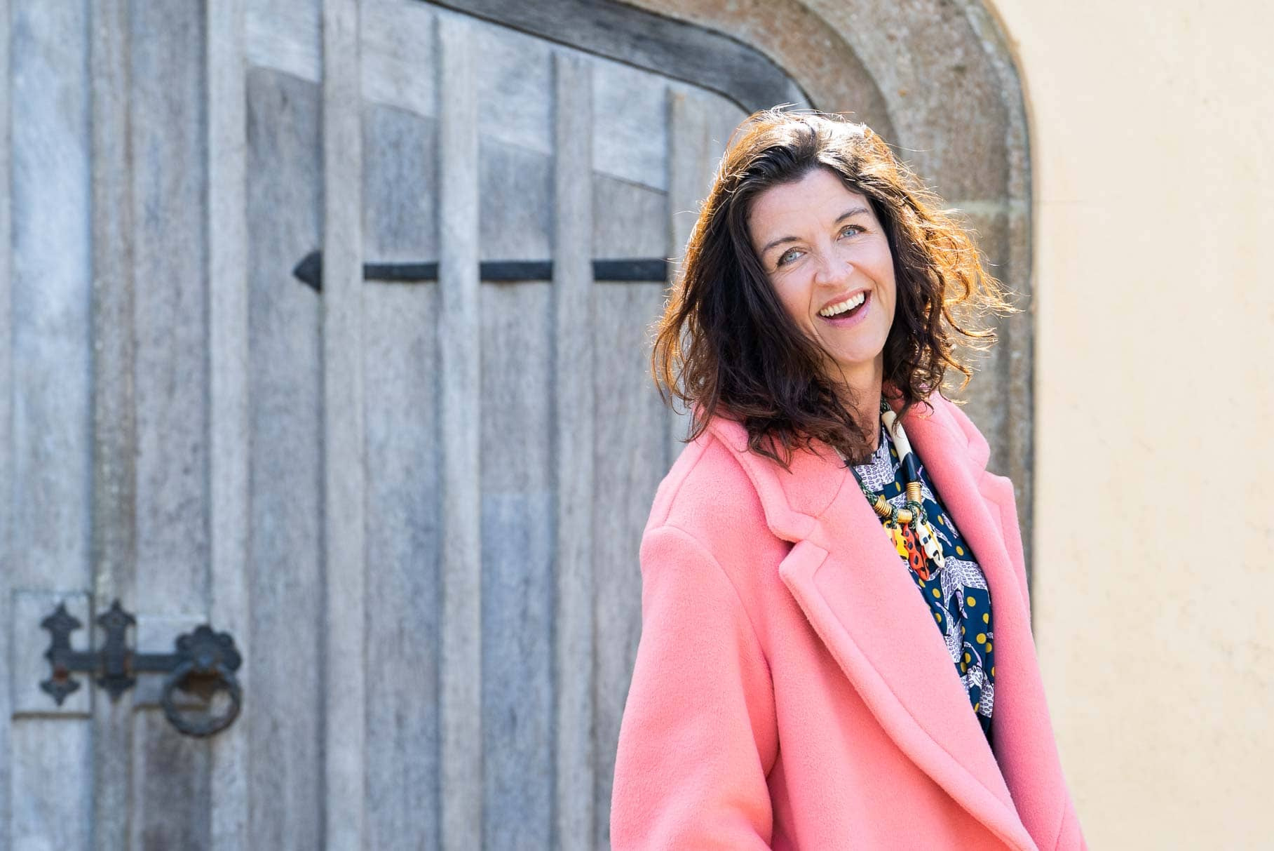 business woman on a branding photography shoot wearing a bright pink coat